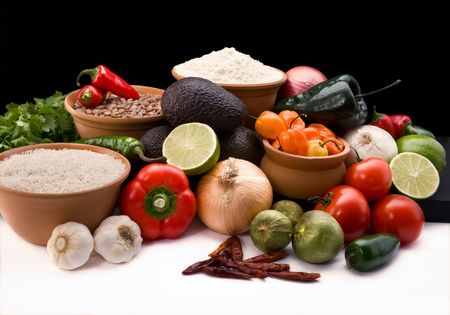 onions: attractive display of all of the fresh ingredients, peppers, onions, tomatoes, avacodos, rice, and beans for creating  traditional mexican cruisine on a black background