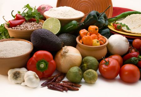 onions: attractive display of all of the fresh ingredients, peppers, onions, tomatoes, avacados, rice, and beans for creating  traditional mexican cruisine on a white background Stock Photo