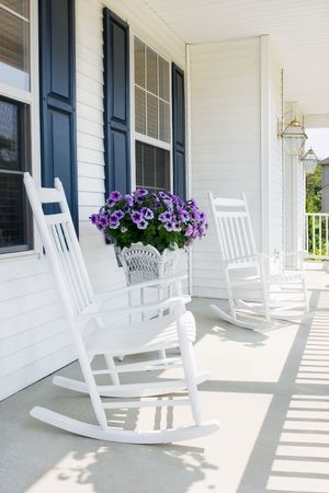 white rocking chairs with purple petunias on a suburban covered porch photo