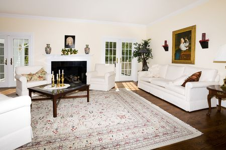 oriental rug: Luxurious Living room with fireplace, oriental rug on wood floor, religious pictures, candle sticks