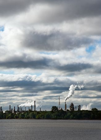 zoning: Industrial landscape including river in foreground and factory smokestacks on horizon against an ominous sky.