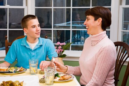 Happy mother and her teenage son eating at the dinner table photo