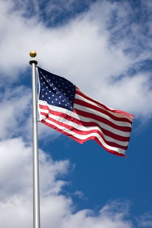 americal: Americal flag blowing in wind with blue sky and white clouds background