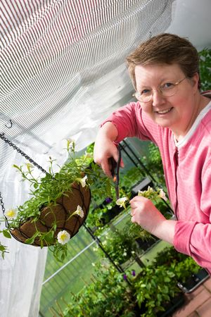 Woman trims flowers and plants in greenhouse. photo