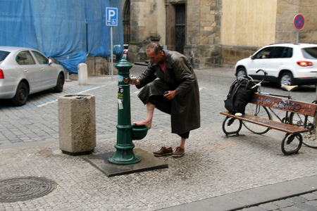 Homeless person washing his feet on the street in Prague