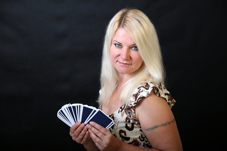 fortuneteller: Blond lady with cards, Fortune-teller, black background Stock Photo