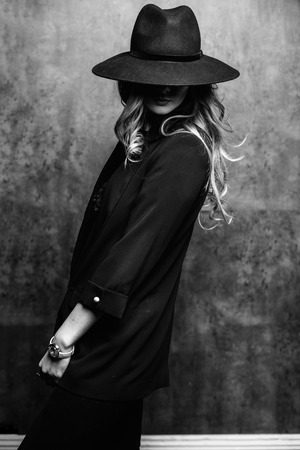 Schönes junges mysteriöses blondes Mädchen im schwarzen Hut und in der schwarzen Jacke auf grauem Hintergrund. Die Augen sind mit einem Hut bedeckt. Maniküre - lange rote Nägel, Nagellack. Mode, Schönheit.