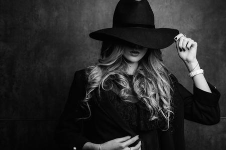 Mooi jong mysterieus blond meisje in zwarte hoed en zwart jasje op grijze achtergrond. Ogen zijn bedekt met een hoed. Manicure - lange rode nagels, nagellak. Mode schoonheid.