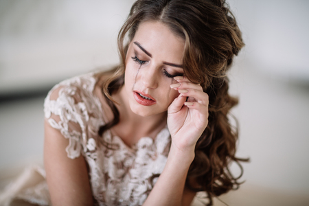 portrait of the bride crying, sadness, streaks mascara wipes. Natural light