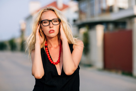Portrait of a girl blonde in a black dress eyes glasses on the neck of the red beads. Holding his right hand to finger the beads. Natural light solar