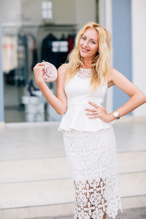 blonde girl at the store where discounts in white dress Stock Photo