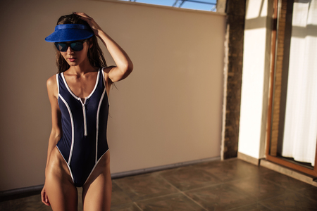 Beautiful girl brunette in sunglasses in blue one piece bathing suit and hat, sexy, sunlight Фото со стока