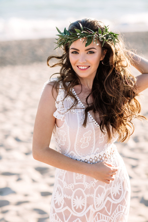 Beautiful girl on the beach in a beautiful dress. Sunny day, white sand, boho.