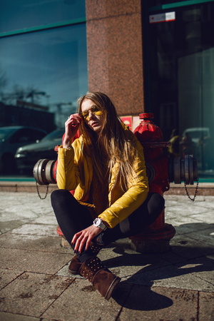 A young European woman, traveling, with long blond hair, wearing a yellow jacket, yellow sunglasses walking down the city center street, street shooting. Even light. Stock Photo
