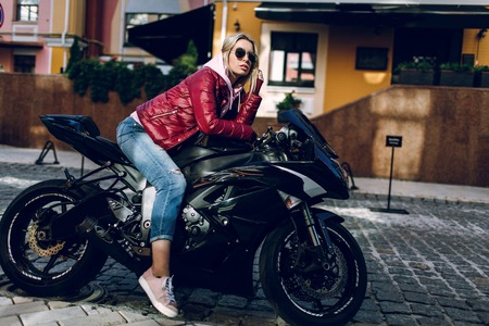 Young beautiful sexy brunette sitting on a black motorcycle with a motorcycle helmet on the street near a modern black building.