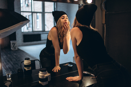 Portrait of a beautiful fashionable woman, blonde, jeans, posing in front of a mirror Фото со стока