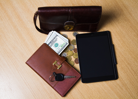 on a wooden table lay money, notebook, tablet, handy bag and the keys to the car. Set of modern business perso