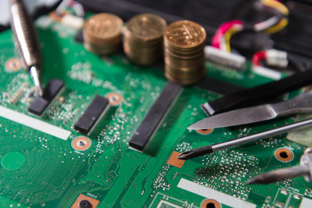 PCB green with tools and coins, a screwdriver, a soldering iron, knife, close up. Components on the motherboard of the laptop. Stock Photo