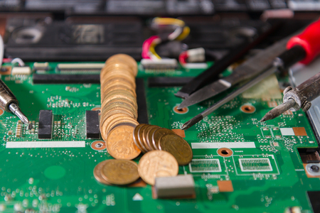 Printed circuit board green with tools and coins closeup. Repair of notebook components