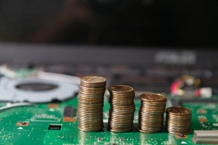 circuit Board notebook green with coins, close up. business concept component repair laptop