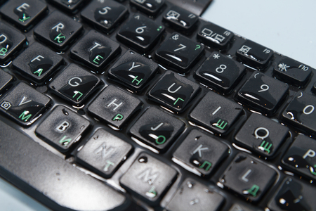 Keyboard black water drops on the buttons, closeup. Duplicate Russian characters