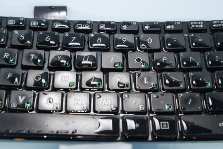 keyboard filled with water on a blue background separately, closeup of a button. Train and duplicate Russian characters Stock Photo