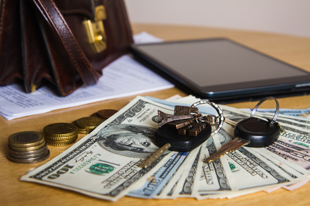 Morning businessmen and business concept, car keys, money, coins, purse, tablet on a wooden table