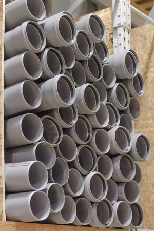 arranged on heap plastic pipes, grey on the shelf is sold in the store
