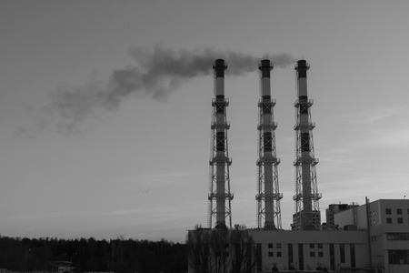 Industrial view - Thermal power station with pipes in the city near the forest. From the chimneys smoke into the sky. ecology concept. black and white photography