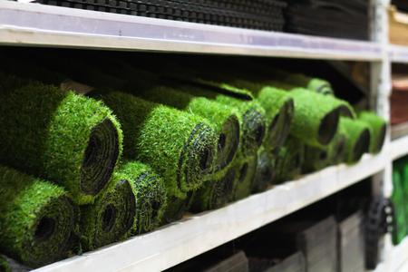 Rolos de venda de grama artificial no supermercado na prateleira Foto de archivo - 93510190