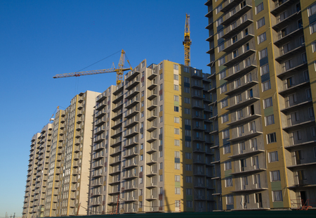 modern multi story residential building with construction crane lifting in the final stages of construction.
