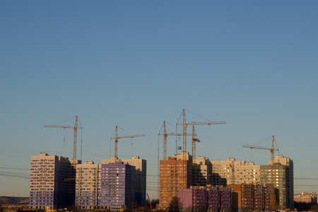 Silhouettes of tower cranes against of residential houses in the microdistrict. Industrial skyline view of the construction, free space on blue sky as background
