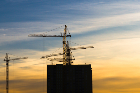 Several cranes crane yellow finish building multi-storey residential building at sunset on blue sky background Stock Photo