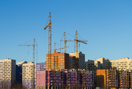 The building of a residential district of multi-storey houses with elevating cranes of yellow color on a background of blue sky. Conceptual