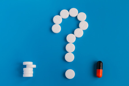 The tablets are white meds on a blue background. A symbol of a question mark. Choose between multiple pills and medical pills. Conceptual for pharmaceutical Stock Photo