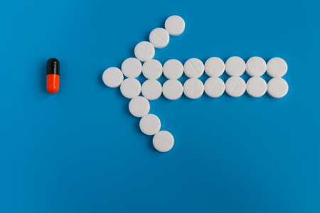 Pill white round medications laid out in the shape of an arrow points to the black colored pill with orange. Conceptual for pharmaceutical production.