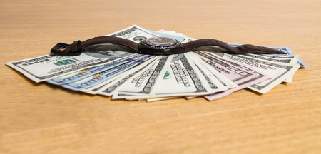 Time is money, hand watch one hundred dollar bills are spread out in a fan. lie on the table Stock Photo