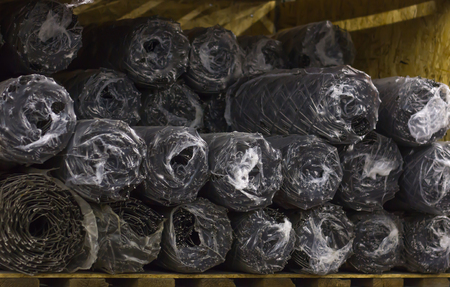 Rolls of wire mesh steel for construction lie on the shelf of the warehouse, steel wire tie for construction site. Stock Photo