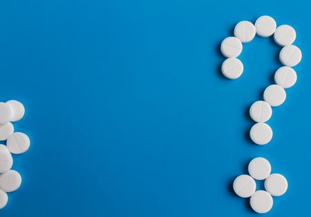 White medical pills question mark on blue background, conceptual image. Medications for the treatment of patients. Custom and unique photo