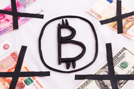 Bitcoin is made of plastic surrounded by crossed out banknotes of different countries. Unique and original image of the symbol. Non-standard concept Stock Photo