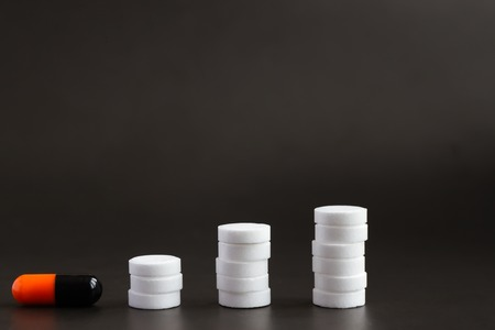 white tablets lined with towers of different heights and a pill of black and orange medicine. pharmacy, steps from pills on a gray background Stock Photo