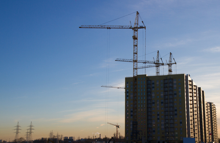 Construction cranes build high houses, near free space