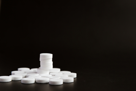 lot of drugs with a pyramid of white pills lie on a black background. pharmaceutical concept Stock Photo