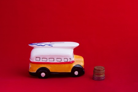 piggy bus ceramic bus near coins. the concept of saving money and saving. Red background Stock Photo
