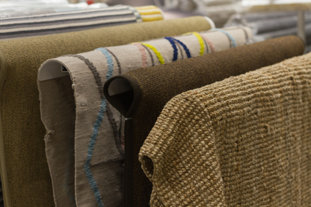 New carpets hang in the mall. Selection of carpets Stock Photo
