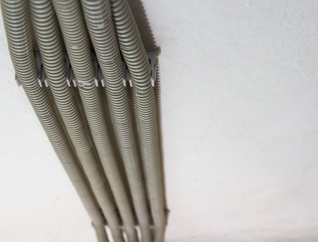 A close-up of several corrugated gray pipes are fixed to the ceiling with clips. Protective white PVC corrugated pipe channels w