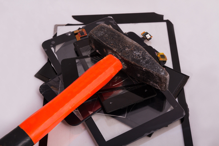 broken touchscreens lie a bunch of them on a hammer. service for gadget repair. concept