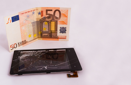 A broken touchscreen with a display and a euro banknote. isolated on white background
