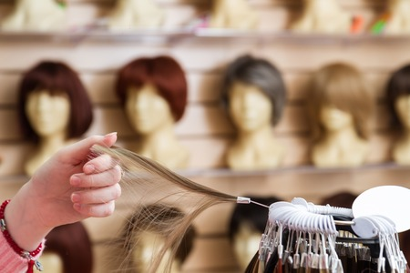 girl in her hand chooses a hair color wig of a natural blond. A palette of hues of hair color in a store of wigs on a blurry Stock Photo
