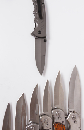 folding knife blade blades little across from lies one folding knife. Hunting or marching sharp knife and part of the handle. Stock Photo